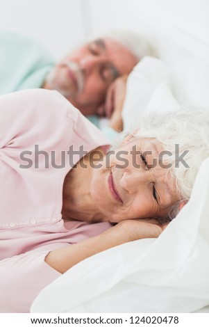 Elderly couple asleep in bed