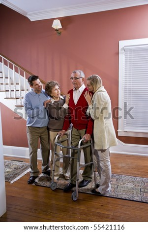 Elderly couple at home with adult children, senior man using walker