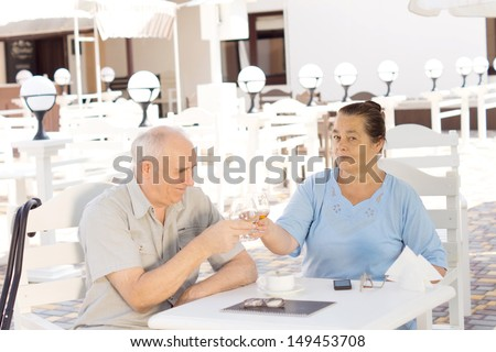 Elderly couple celebrating toasting and clinking their glasses while enjoying a drink at an outdoor restaurant - stock photo