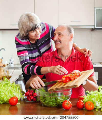 elderly couple cooking with tomatoes in kitchen at home