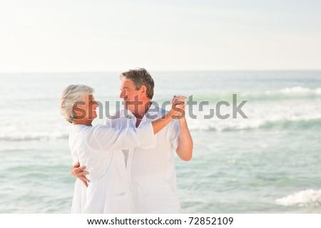 Elderly couple dancing on the beach - stock photo