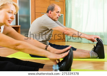 Elderly couple doing exercises in the living room at home. Focus on man  - stock photo