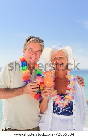 Elderly couple drinking a cocktail on the beach - stock photo