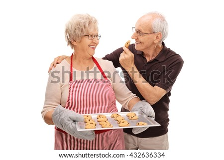 Elderly couple eating homemade chocolate chip cookies isolated on white background  - stock photo