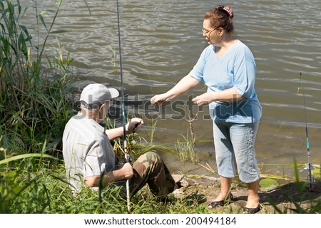 Elderly couple fishing on a freshwater lake with the man seated on the bank with his rod as his wife assists him