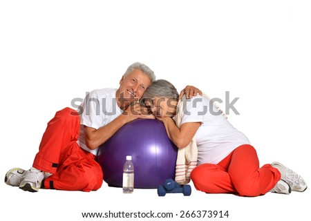 Elderly couple having a rest on a floor of a gym isolated on white - stock photo