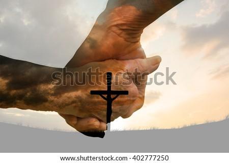 Elderly couple holding hands against cross religion symbol shape over sunset sky - stock photo