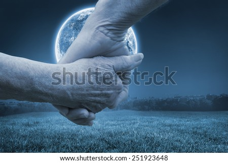Elderly couple holding hands against large moon over paris - stock photo