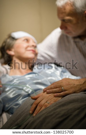 Elderly couple holding hands at clinic ward bed - stock photo