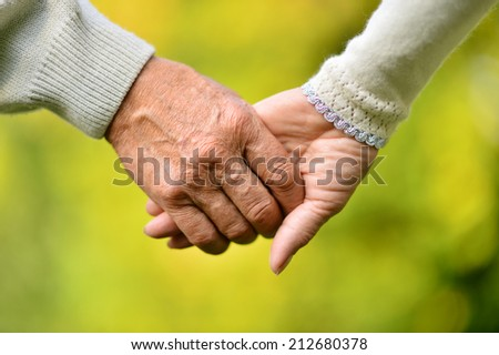 Elderly couple holding hands over natural background - stock photo