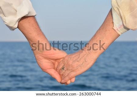Elderly couple holding hands over sea background - stock photo
