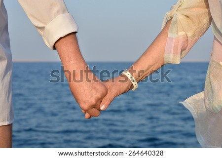 Elderly couple holding hands over sea background