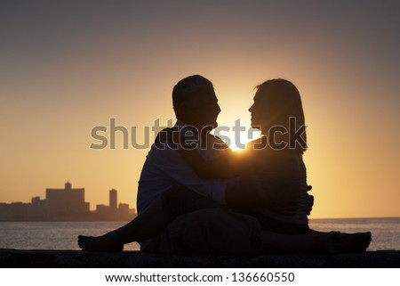 Elderly couple in love, honeymoon with old man and woman kissing near the sea at sunset in La Habana, Cuba. Silhouette of couple and skyline of the city - stock photo