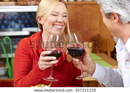 Elderly couple in restaurant cheering with red wine