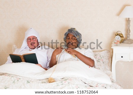 Elderly couple in vintage clothing reading and knitting in bed - stock photo