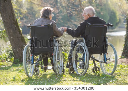 Elderly couple in wheelchairs, holding hands - stock photo