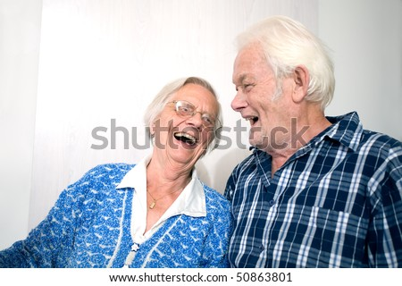 Elderly couple looking at each other laughing. - stock photo