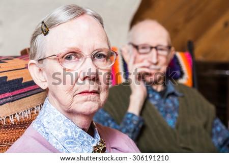 Elderly couple looking seriouds seated in livingroom - stock photo