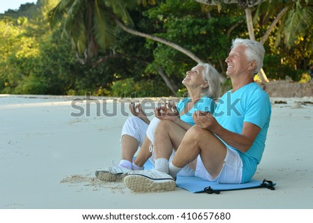 elderly couple meditate on beach