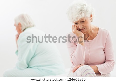 Elderly couple not talking to each other in bedroom