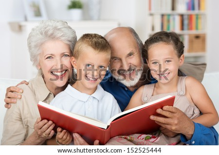 Elderly couple reading to their grandchildren as they all sit close together on a sofa - stock photo