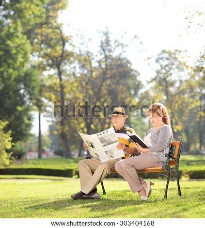 Elderly couple relaxing on a beautiful day in park.The newspaper is custom made, text is Latin and the pictures are my copyright. Additionally property release uploaded. - stock photo