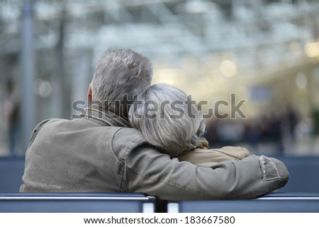 Elderly couple relaxing on a bench. back view - stock photo