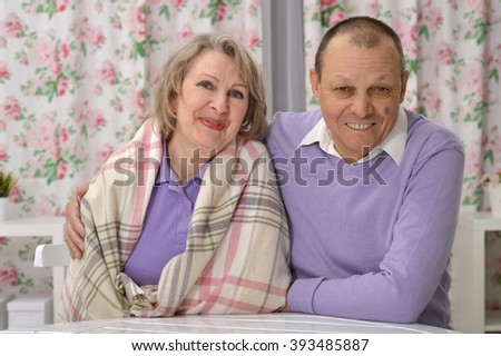 elderly couple resting at his desk