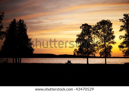 Elderly couple, silhouetted,  sitting on a bench by lake at sunset - stock photo
