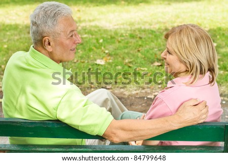 Elderly couple sitting and talking on park bench.