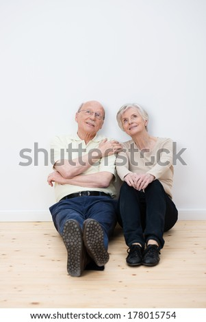 Elderly couple sitting daydreaming on the bare wooden floor in their living room in their new home as they imagine the placement of their personal belongings - stock photo