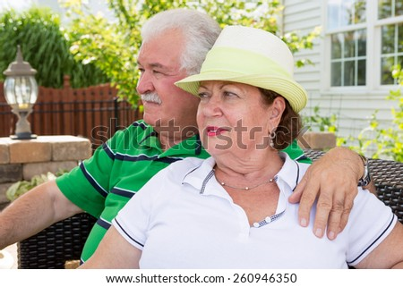 Elderly couple sitting on a wicker settee on an outdoor patio gazing into the distance watching something with serious expressions - stock photo