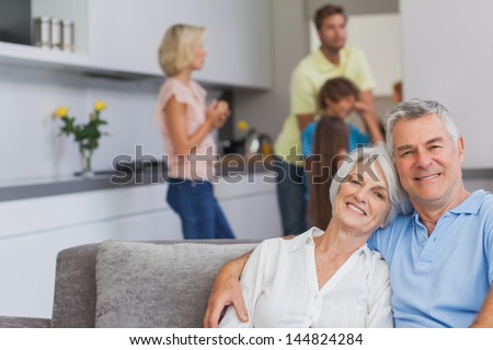 Elderly couple sitting on the couch and smiling at camera while their family is standing in the kitchen behind - stock photo