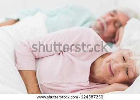Elderly couple sleeping in bed - stock photo