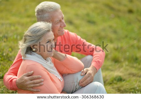 Elderly couple smilling together over natural background - stock photo
