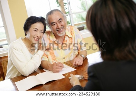 Elderly Couple Speaking to Salesman - stock photo