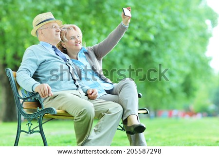 Elderly couple taking a selfie in the park seated on a bench - stock photo
