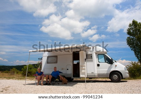 Elderly couple travel by camping car - stock photo