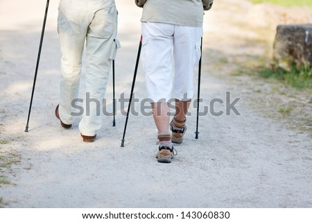 Elderly couple traveling with nordic walking sticks, walking together. - stock photo