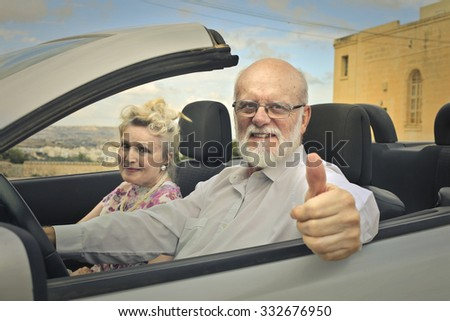 Elderly couple travelling by car - stock photo
