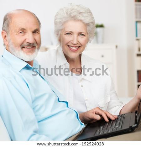 Elderly couple using a laptop computer as they sit side by side on a couch sharing the internet and smiling at the camera - stock photo