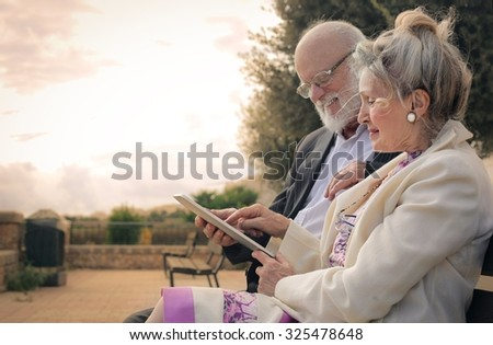 Elderly couple using a tablet - stock photo