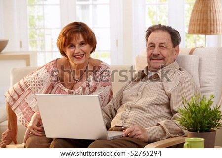 Elderly couple using laptop computer at home, looking at camera, smiling.