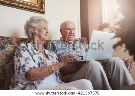 Elderly couple using laptop computer at home. Senior man and woman sitting on sofa working on laptop. - stock photo
