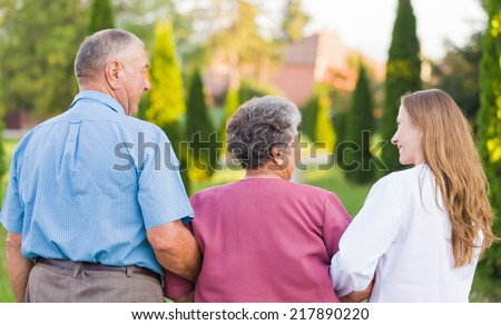 Elderly couple walking in the nature with the carer - stock photo