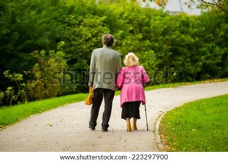 Elderly couple walking together. - stock photo