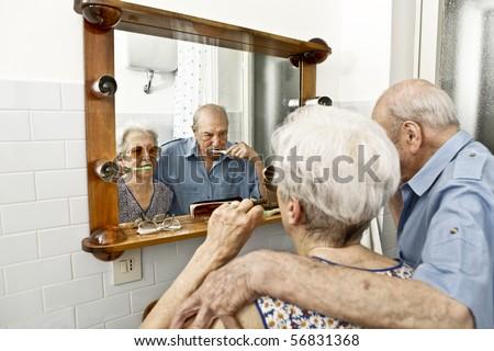 elderly couple washing teeth - stock photo