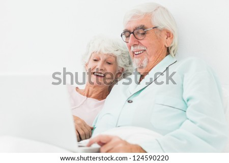 Elderly couple watching something on laptop in bed