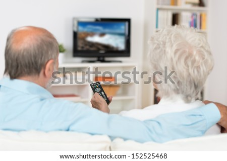 Elderly couple watching television sitting comfortably on a sofa with their backs to the camera holding the remote control - stock photo