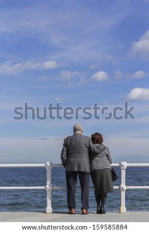 Elderly couple waterfront  - stock photo